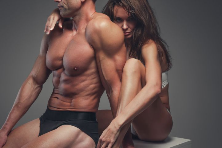57250170 - beautiful fitness couple posing in a studio.